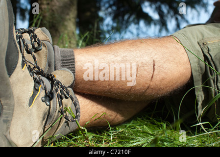 Man in hiking boots relaxing on grass with legs crossed, low section - Stock Photo