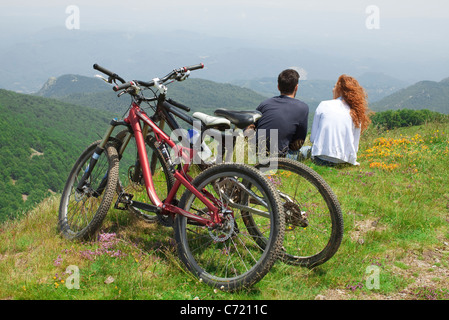 Couple sitting together on hill, looking at view, bicycles parked behind them - Stock Photo