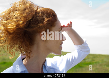 Young woman looking into distance, hand shading eyes - Stock Photo