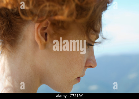 Redheaded woman with hair up, side view - Stock Photo