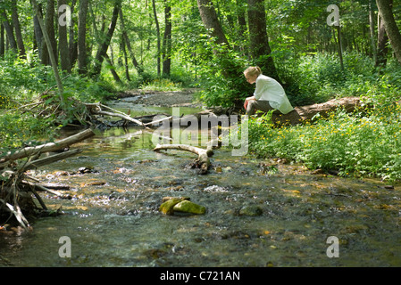 Young woman sitting by river running through woods - Stock Photo