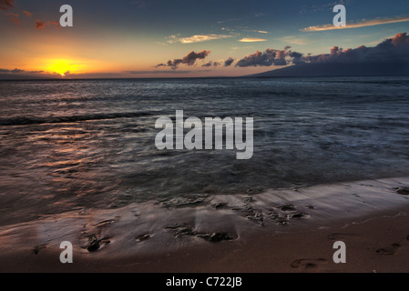 Sunset on a beach on Kaanapali Maui Hawaii showing the colorful sky colors with the island of Molokai in the distance - Stock Photo
