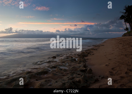 A beautiful Maui sunset with clouds in the distance and waves lapping over the coral on the beach - Stock Photo