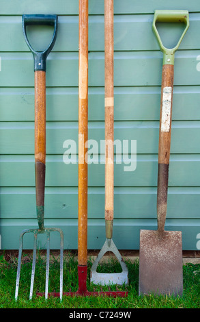 Well used garden/ gardening tools leaning against the side of a garden shed - including a  fork, rake, hoe and spade. - Stock Photo