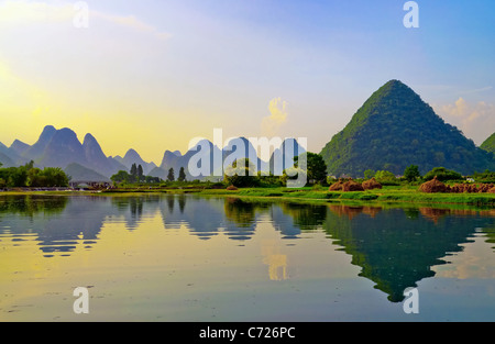 Reflection of the muntains in Li River landscape on sunset, Yangshuo near Guilin, China - Stock Photo