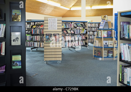 Inside a public library with books on book shelves. Wales, UK, Britain.