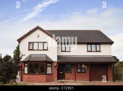 Outside of a detached four bedroomed residential house front with brick paved driveway and integral garage. Executive - Stock Photo