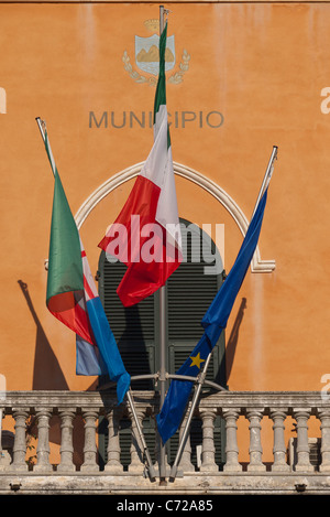 Three flags, Monterosso al Mare, the Italian and the European Union flags are positioned in front of the municipal - Stock Photo
