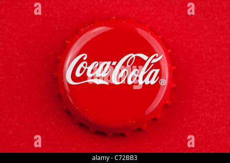 Muenster, Germany - September 10, 2011: Picture shows coca cola bottle cap on red background. - Stock Photo