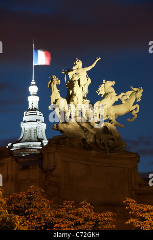 A huge floodlit bronze sculpture by Georges Récipon of a quadriga, a chariot drawn by four horses, atop the Art - Stock Photo