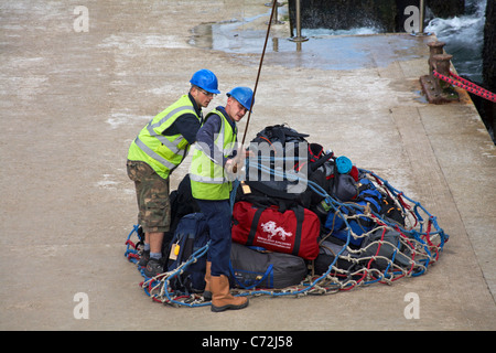 Two workmen netting up luggage to load onto M.S. Oldenburg for staying visitors to Lundy Island on quayside at Ilfracombe, - Stock Photo