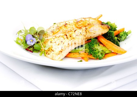 Fresh black cod on bed of broccoli and carrots with a touch of micro herbs - Stock Photo