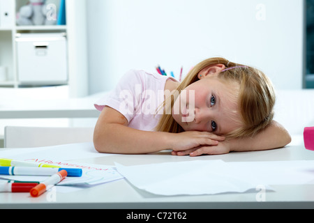 Portrait of lovely girl putting her head on desk - Stock Photo