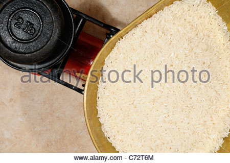 Rice grains on Kitchen scales, England - Stock Photo