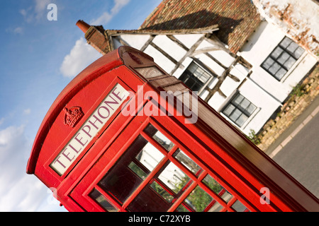 A traditional English Village red Telephone Box - Stock Photo