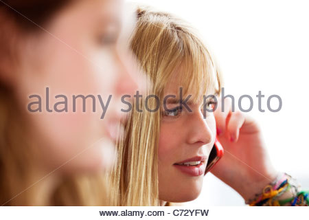 Two teenage girls sitting on a bus, one girl talking on her mobile phone - Stock Photo