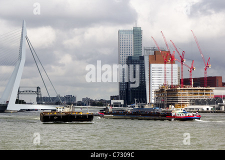 Busy water transport with freight barges on the Nieuwe Mass river, Rotterdam. Backdrop is the Erasmus Bridge and - Stock Photo