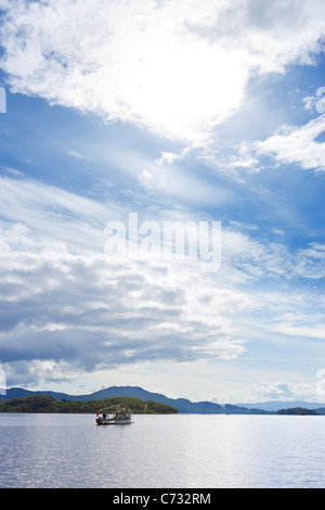 Fishing boat on the loch viewed from Luss on the west bank of Loch Lomond, Argyll and Bute, Scotland, UK - Stock Photo