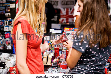 Two teenage girls looking at souvenirs of London - Stock Photo