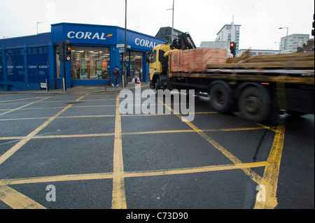A big lorry crossing the box junction and turning into another street. - Stock Photo