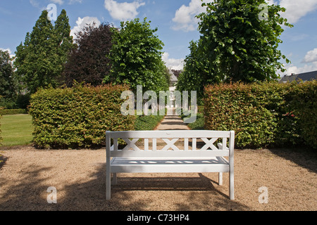White garden bench in front of a row of trees, Borchers Garden, private garden in Goslar, Lower Saxony, Germany - Stock Photo