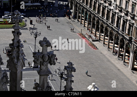 Looking at piazza Duomo through one of the decorations on Milan Cathedral (Duomo di Milano) roof - Stock Photo