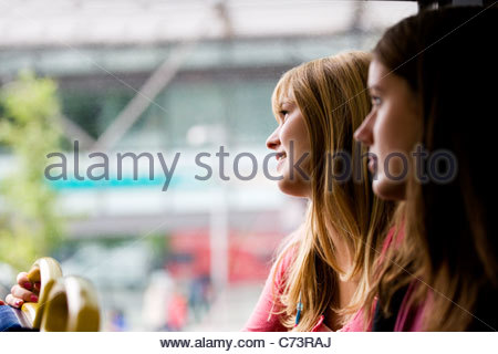 Two teenage girls sitting on a bus, one girl looking out of the window - Stock Photo