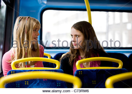 Two teenage girls sitting on a bus, having a conversation - Stock Photo