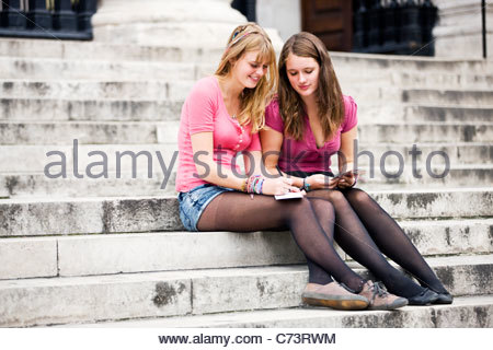 Two teenage girls sitting on steps, writing postcards - Stock Photo