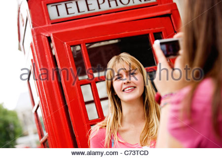 A teenage girl taking a photograph of her friend in front of a telephone box - Stock Photo