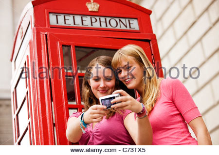 Two teenage girls taking a photograph of themselves in front of a telephone box - Stock Photo