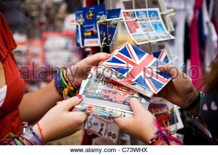 Two teenage girls choosing postcards in a souvenir shop - Stock Photo