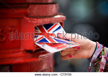 A teenage girl putting postcards into a red letterbox - Stock Photo