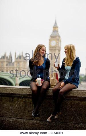 Two teenage girls sitting near Big Ben, having lunch - Stock Photo