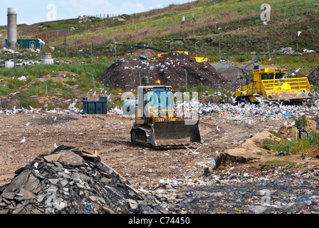Bulldozer working in landfill site and seagulls with methane gas burner in the background. - Stock Photo