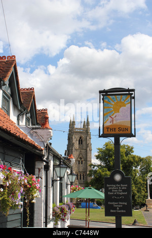 The sign of the Sun pub with St Thomas a Becket Church in background – Northaw Village, Hertfordshire during summer. - Stock Photo