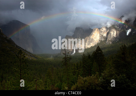 A beautiful rainbow appears over Yosemite Valley following a rain storm. - Stock Photo
