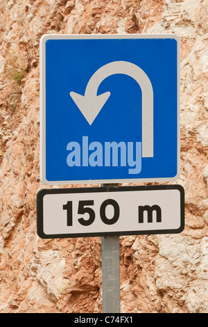 Road sign warning of a sharp bend 150 metres further on. - Stock Photo
