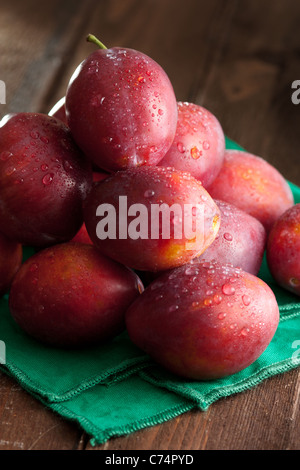 Fresh Plums Pyramid with Green Napkin on Wood - Stock Photo