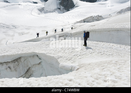 Climbers walking among crevasses on the Vallee Blanche glacier in Chamonix, France - Stock Photo