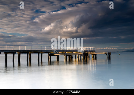 Sunbeams on the pier at Davey's Bay, during the last light - Stock Photo