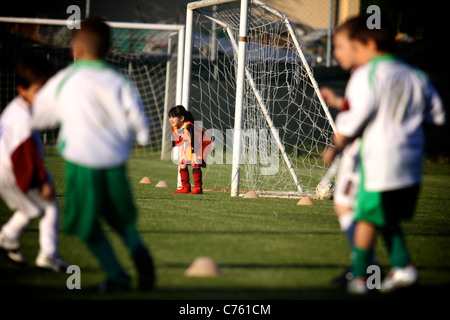 little soccer goalkeeper girl standing on the front of the goal waiting the game. - Stock Photo
