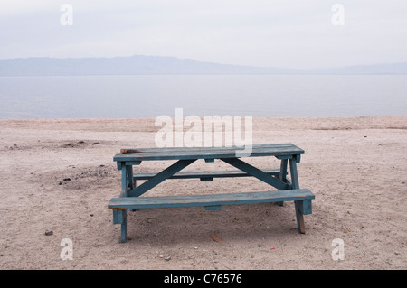 A sloping empty blue wooden picnic table overlooking the Salton Sea, California, USA. - Stock Photo