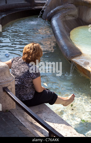 Tourist paddling barefoot in the Barcaccia Fountain at the foot of the Spanish steps Rome - Stock Photo