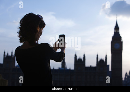 UK, London, Mid adult woman taking picture of Big Ben - Stock Photo