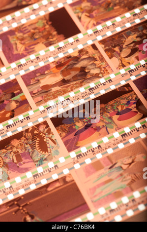 Strips of 35mm colour negative film on a light box - Stock Photo