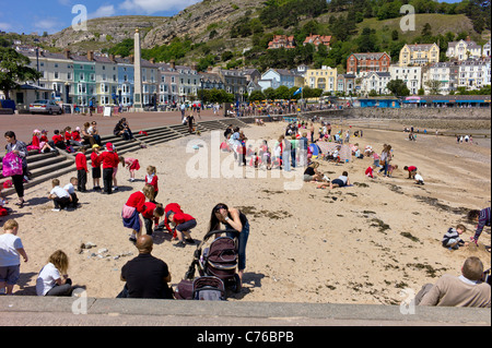 A party of school children visit Llandudno beach, with teachers and assistants, mingle with visitors on a sunny - Stock Photo