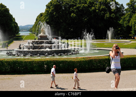 Woman taking a photo in front of the Latona Fountain, Herrenchiemsee Herreninsel Upper Bavaria Germany - Stock Photo