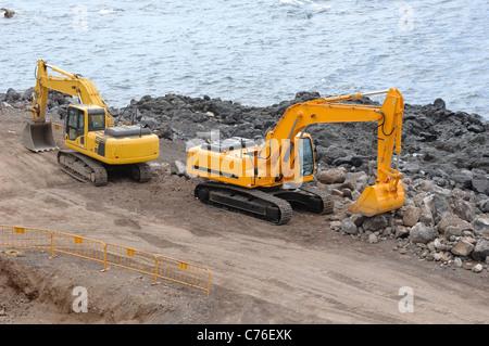 Two orange excavators near the sea - Stock Photo