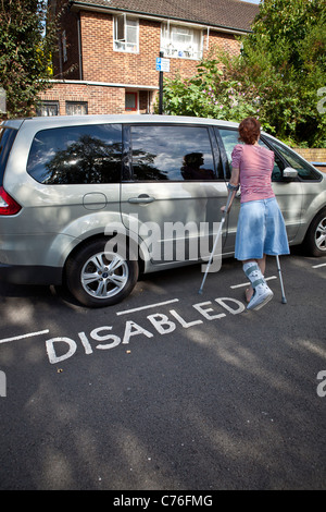 Woman with broken leg unlocking car door parked in disabled parking bay. - Stock Photo